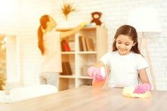 妈妈和女儿在家清洗 抹架子和桌 库存照片