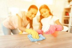 妈妈和女儿在家清洗 抹架子和桌 免版税库存图片