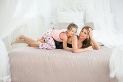妈妈和女儿在床上 在妈咪的背面女孩 库存图片