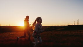 妈妈和女儿在日落赛跑 与孩子的愉快的时间,活跃生活方式 影视素材