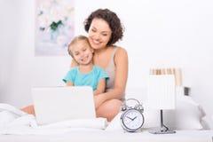 妈妈和女儿在有膝上型计算机的卧室 免版税库存照片