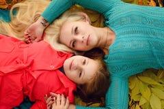 妈妈和女儿在秋天森林里 库存照片
