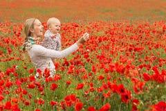 妈妈和女儿在草甸 库存照片