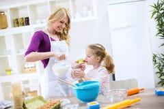 妈妈和女儿在蛋糕投入了牛奶 库存照片