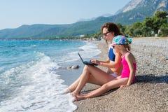妈妈和女儿坐海滩 免版税库存图片