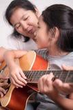 妈妈和女儿弹吉他 库存照片