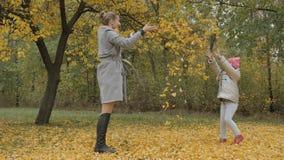 妈妈和女儿投掷黄色叶子 免版税库存照片