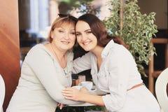 妈妈和女儿是在咖啡馆 免版税库存照片