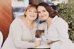 妈妈和女儿是在咖啡馆 免版税图库摄影