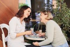 妈妈和女儿是在咖啡馆 免版税库存图片