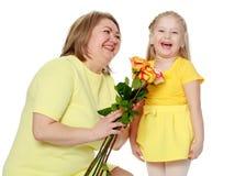 妈妈和女儿有香水月季花束的  免版税库存图片