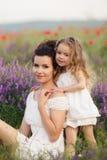 妈妈和女儿淡紫色领域的 免版税图库摄影