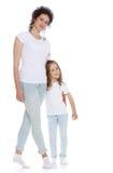 妈妈和女儿牛仔裤白色衬衣的 免版税图库摄影