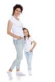 妈妈和女儿牛仔裤白色衬衣的 库存图片