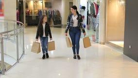 妈妈和女儿皮夹克的在购物中心走与纸袋 股票视频