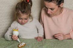 妈妈和女儿装饰与结冰的姜饼 库存图片
