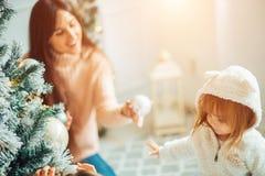 妈妈和女儿装饰圣诞树户内 库存图片