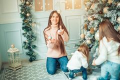 妈妈和女儿装饰圣诞树户内 图库摄影