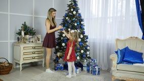 妈妈和女儿装饰圣诞树 库存照片