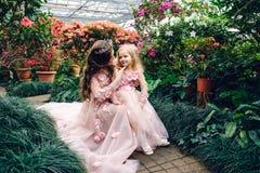 妈妈和女儿豪华桃色的礼服的在一个用花装饰的庭院里 免版税图库摄影