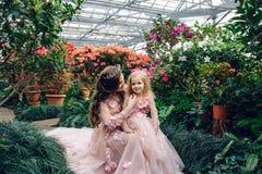 妈妈和女儿豪华桃色的礼服的在一个用花装饰的庭院里 免版税库存图片