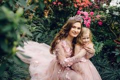妈妈和女儿豪华桃色的礼服的在一个用花装饰的庭院里 库存照片