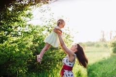 妈妈和女儿跳舞本质上一起在日落光 免版税库存照片
