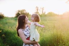 妈妈和女儿跳舞本质上一起在日落光 免版税库存图片