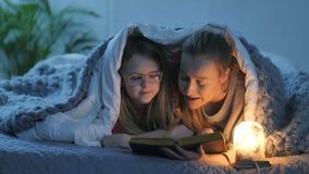 妈妈和女儿阅读书在毯子下的床上 股票视频