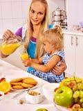 妈妈和女儿食用早餐在厨房 库存图片