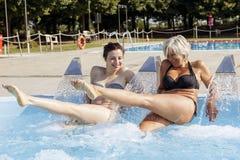 妈妈和女儿,当喷洒在旋涡木盆时的水 免版税图库摄影
