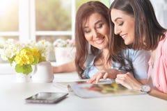 妈妈和女儿读了一本杂志 免版税库存照片
