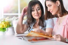 妈妈和女儿读了一本杂志 库存照片