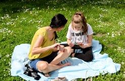 妈妈和女儿织法花圈 库存照片