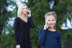 妈妈和女儿 电话交谈 免版税库存图片