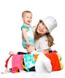 妈妈和女婴有手提箱和衣裳的准备好旅行 库存图片