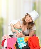 妈妈和女婴有手提箱和衣裳的准备好旅行 免版税库存图片