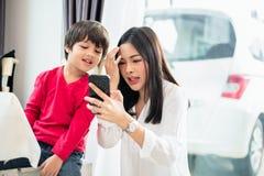妈妈和她的一起使用和调查智能手机的孩子 人和技术概念 教育和学习题材 免版税库存照片
