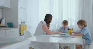 妈妈和她的两个儿子在画色的铅笔家庭的厨房用桌上画坐草坪在夏天 影视素材