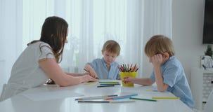 妈妈和她的两个儿子在画色的铅笔家庭的厨房用桌上画坐草坪在夏天 股票录像
