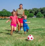 妈妈和她的两个儿子在草坪踢橄榄球 免版税图库摄影