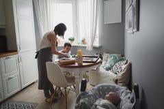 妈妈和她的儿子在舒适家庭厨房里烹调曲奇饼 在观看一个新出生的婴孩的他们旁边 库存照片