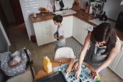 妈妈和她的儿子在舒适家庭厨房里烹调曲奇饼 在观看一个新出生的婴孩的他们旁边 免版税库存照片