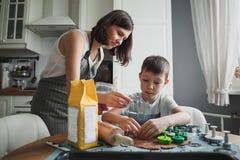 妈妈和她的儿子在舒适家庭厨房里烹调曲奇饼 菜油细流在特写镜头的 免版税库存照片
