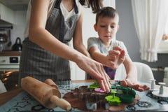 妈妈和她的儿子在舒适家庭厨房里烹调曲奇饼 免版税库存照片
