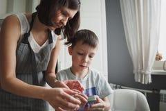 妈妈和她的儿子在舒适家庭厨房里烹调曲奇饼 库存照片