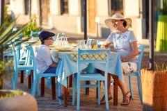 年轻妈妈和她的儿子街道咖啡馆的 免版税库存照片