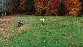 妈妈和她的儿童游戏与球在秋天森林里他们乐趣奔跑并且猛撞球 家庭是 股票视频