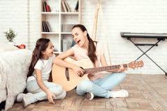 妈妈和她的女儿在家坐地板并且弹吉他 他们唱歌到吉他 图库摄影