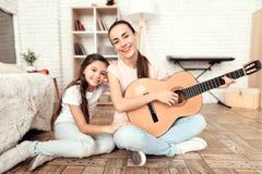妈妈和她的女儿在家坐地板并且弹吉他 他们唱歌到吉他 免版税库存照片